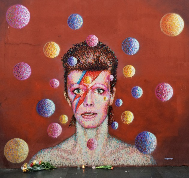 Fans lay flowers and candles at the David Bowie mural on Tunstall Road, Brixton