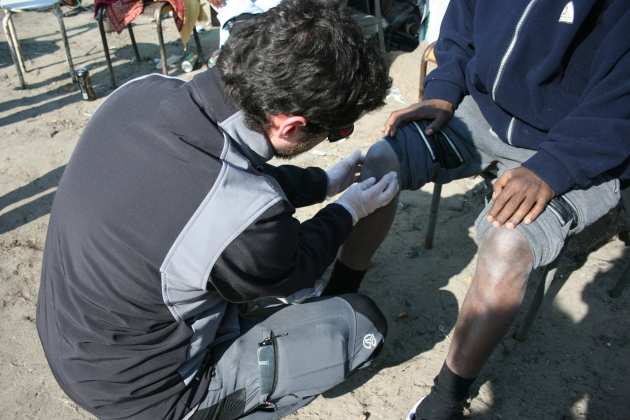 Student paramedic, Javier Garcia-Marcos, examines an Eritrean refugee complaining of knee pain. Photo Credit: Rose Oloumi